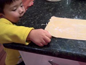 Little A tries to sneak a piece of uncooked pasta