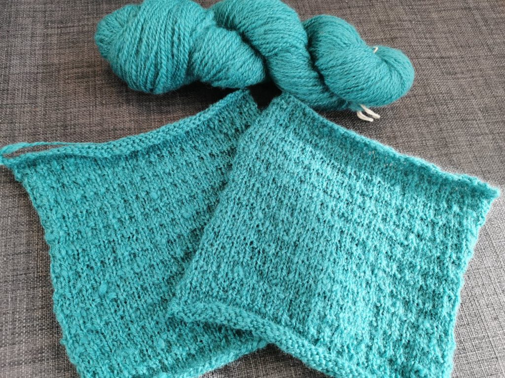 Squares of knitted squares in teal