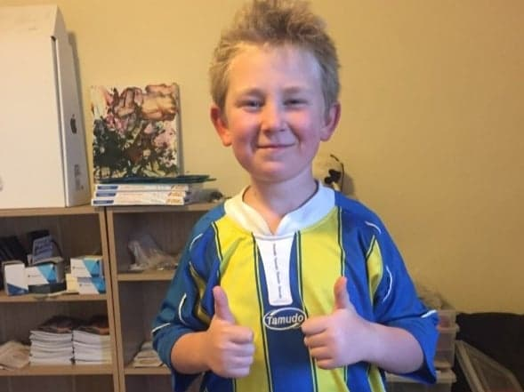 boy with thumbs up wearing a soccer shirt