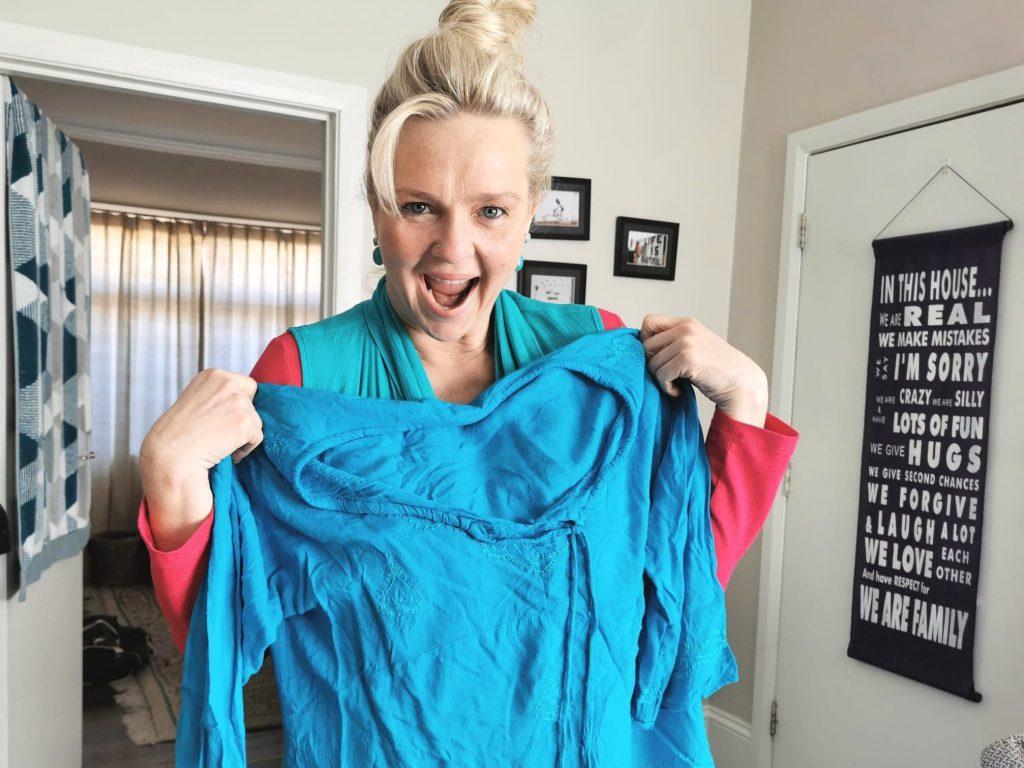 Liz holding up a blue shirt