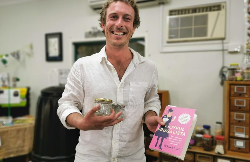 Canberra Environment Centre director holds three glass jars and a copy of The Joyful Frugalista