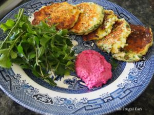 A plate of zucchini fritters with rocket and beetroot dip