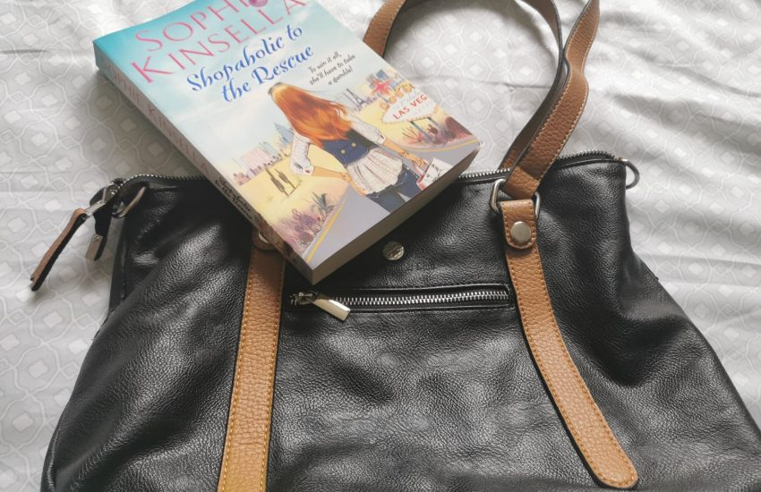 Black and beige handbag and a book