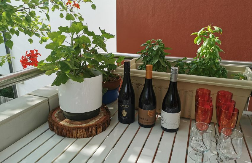 My balcony with wine, glasses, geraniums and basil